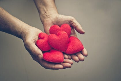 Händer som håller hjärtan