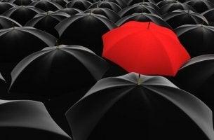 Rött paraply bland svarta