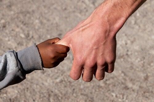 Barn håller mans hand