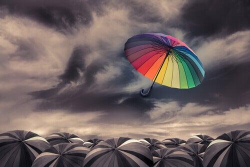 Färgglatt paraply bland grå