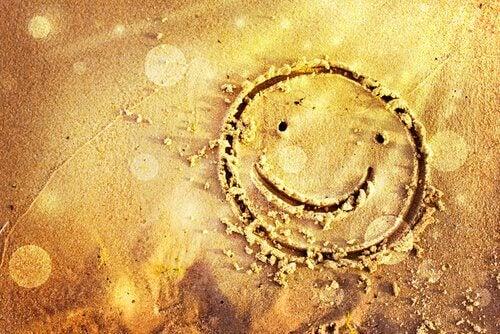 Leende ansikte i sanden