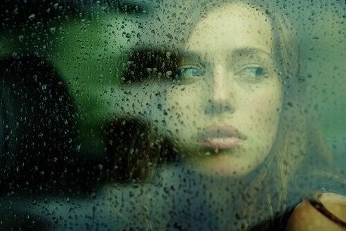 Kvinna vid regnigt fönster
