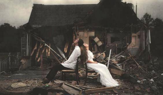 Par framför förstört hus
