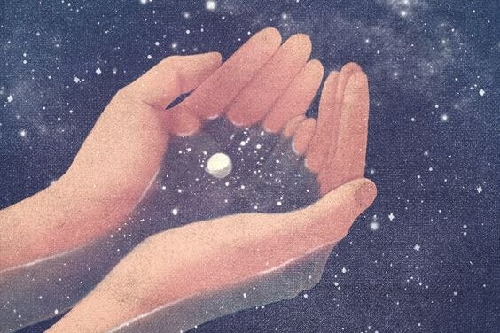 Händer håller universum