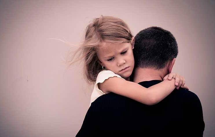 Flicka som kramar sin pappa