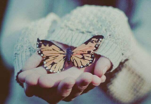 Kvinna med fjäril i handen