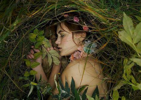 Kvinna som sover bland gräs