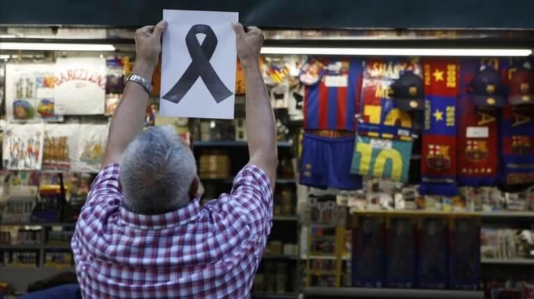 Man som hänger upp svart band efter terrordåd i Barcelona