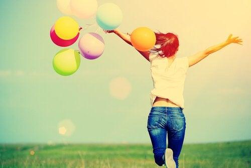 Glad kvinna med ballonger
