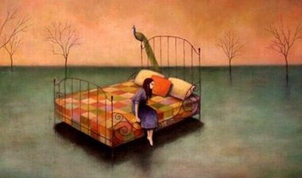 Kvinna som sitter på säng
