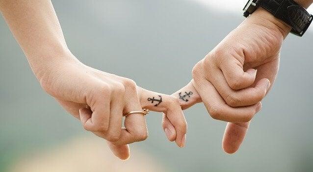 Par som håller finger