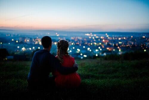 Par som sitter vid solnedgång