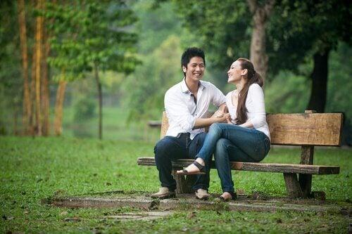 Par som skrattar på bänk