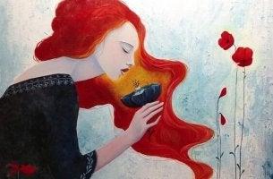 Rödhårig kvinna som luktar på blomma
