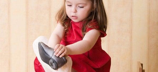 Flicka tar på sig skorna