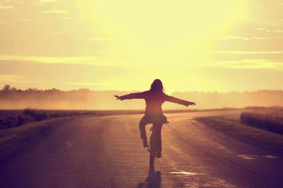 Lycklig kvinna på cykel