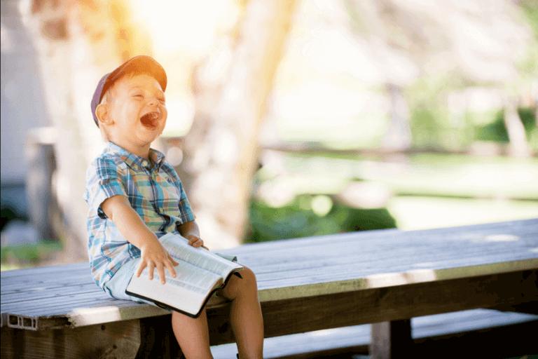 Barn som skrattar med bok
