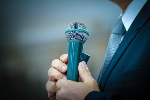 Man i kostym håller en mikrofon