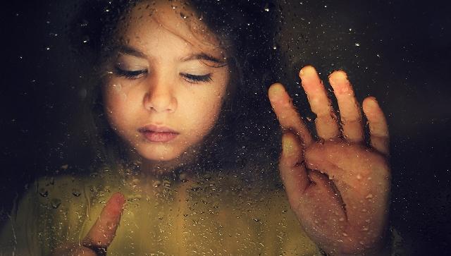 Flicka som håller hand mot fönstret
