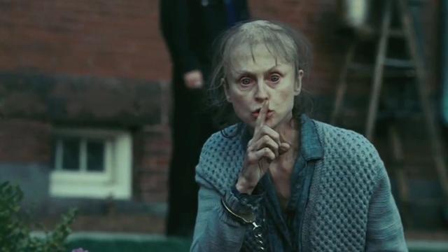 Kvinna som håller finger framför munnen.