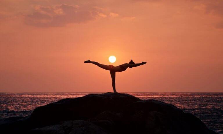 Kvinna som utför yoga vid havet.