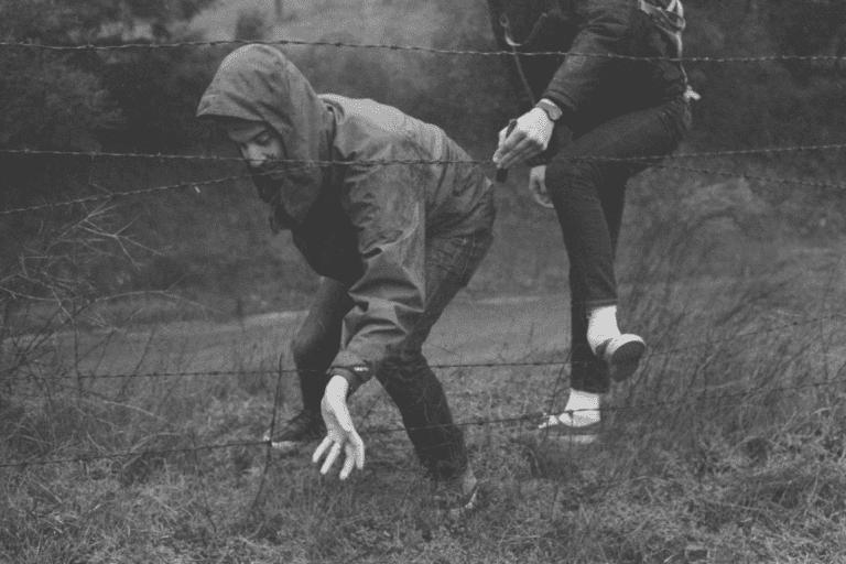 Personer vid taggtrådsstängsel