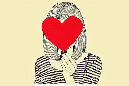 Kvinna håller hjärta över ansiktet