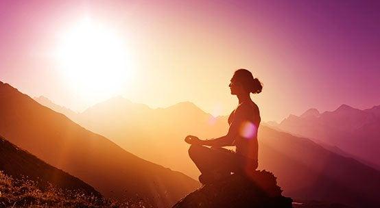 Kvinna mediterar på ett berg