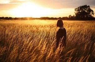 Kvinna som står mitt i ett fält.