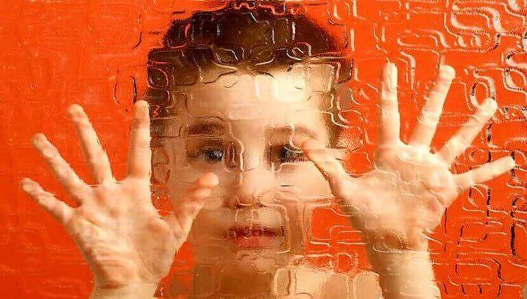 Pojke som står bakom ett fönster.