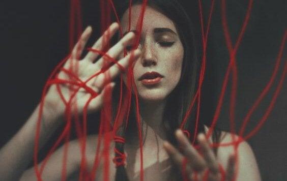 Kvinna bland röda trådar