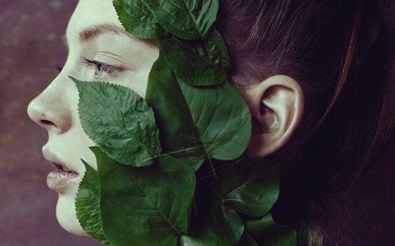 Kvinna täckt av blad