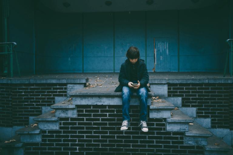 Barn som sitter med sin telefon.