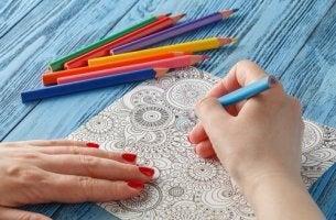 Person färglägger mandalas