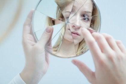 Kvinna ser sig själv i trasig spegel