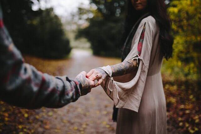 Man som håller kvinna i handen.