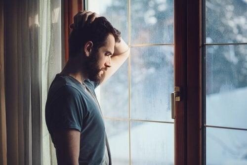 Man som står vid fönster.