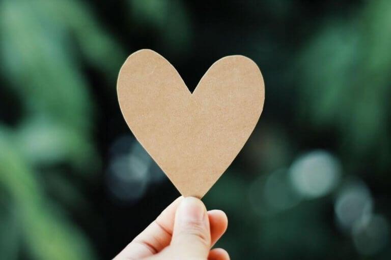 Person som håller i pappershjärta.