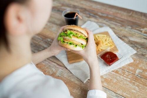 Kvinna äter hamburgare