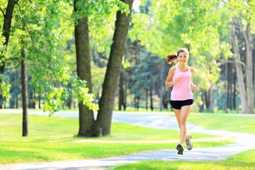 Kvinna som joggar i parken.
