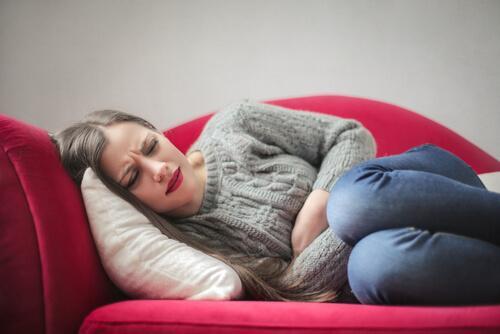 Kvinna som ligger i soffan.