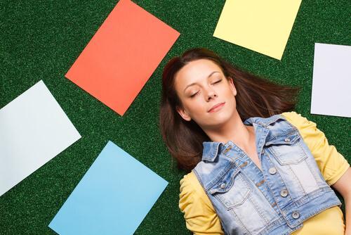 Kvinna som ligger ner bredvid pappersark i olika färger.