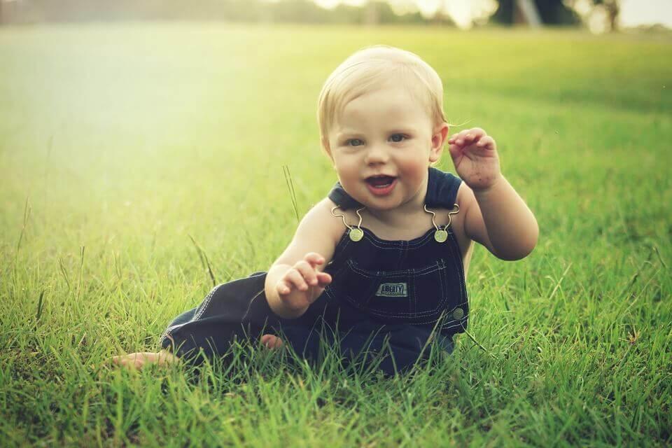 Baby som leker i gräset