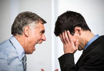 Chef som skriker på anställd.