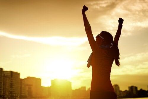 Glad kvinna med armarna uppsträckta i luften