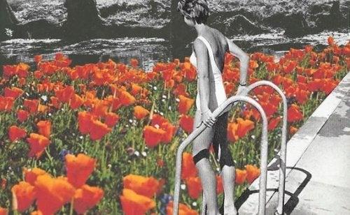 Kvinna stiger ned i pool av blommor