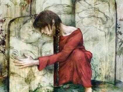 Kvinna kramar gravsten med bild av barn