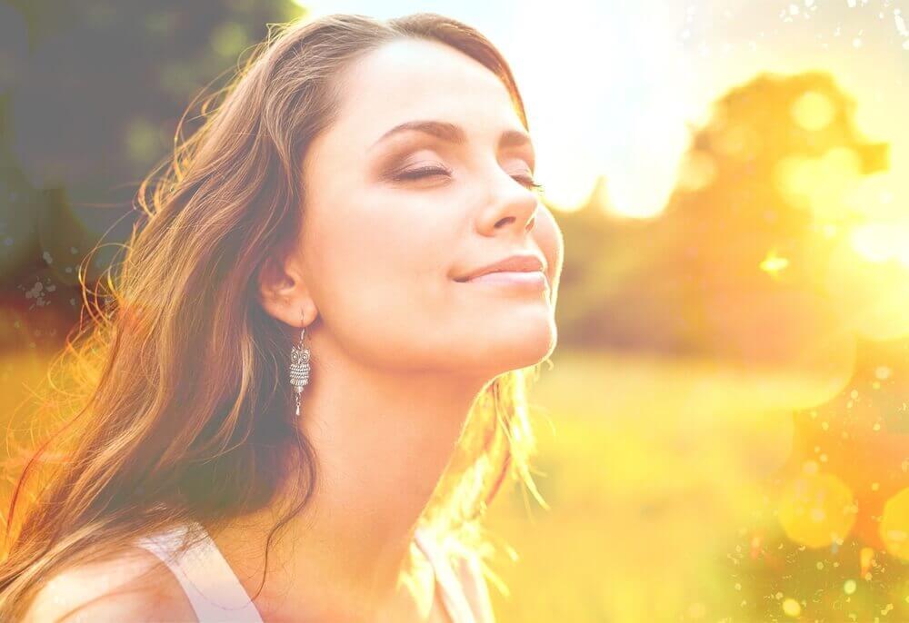 Kvinna med slutna ögon i solen.