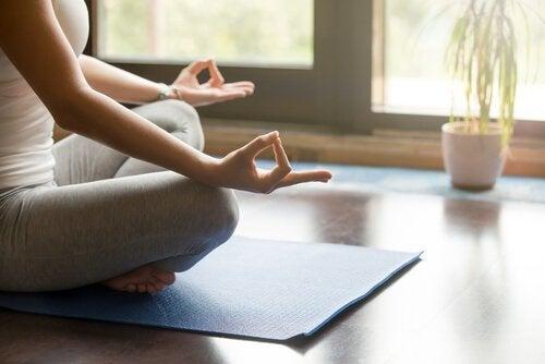 Kvinna mediterar i vardagsrum