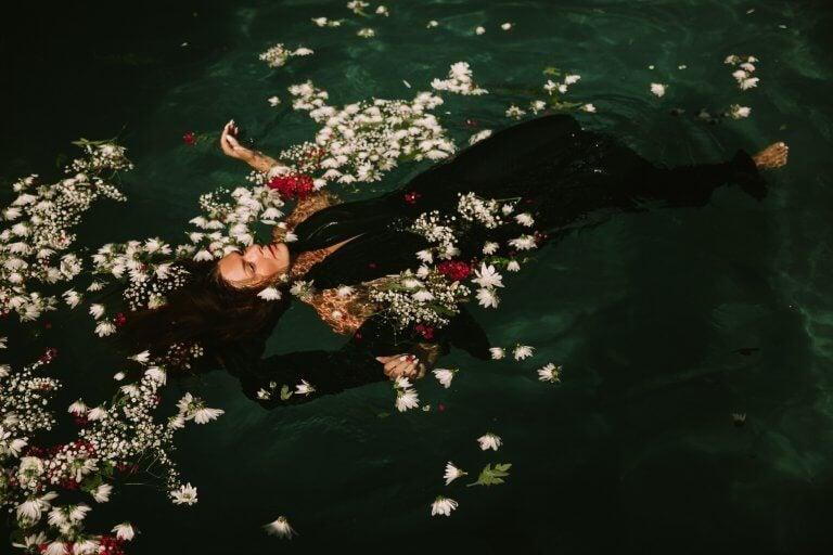 Kvinna som flyter bland blommor.